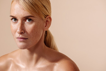Beauty portrait of a young blond woman  Female with freckles looking straight of a camera