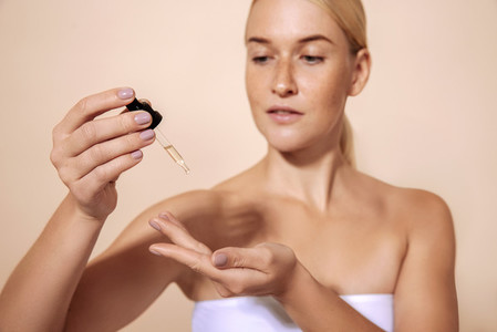 Woman in white towel holding a dropper with hyaluronic acid  Young female trying face serum