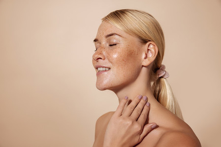 Side view of smiling woman with freckles standing with closed eyes touching her neck