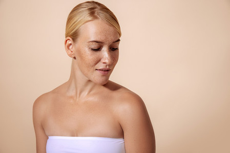 Blond woman with perfect skin looking down in studio against pastel background