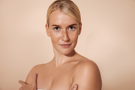 Young woman with perfect skin with freckles posing in studio and looking at camera
