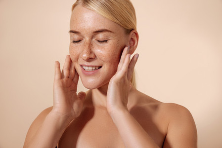 Young smiling woman massaging her face with fingers standing in studio with closed eyes