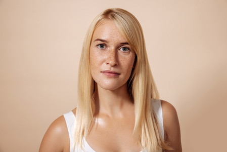 Portrait of young blond woman with freckles standing in a studio looking straight of a camera