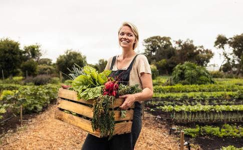Happy female farmer holding a box with fresh produce