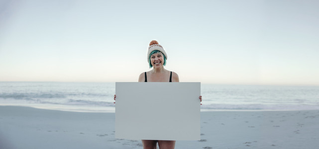 Cheerful winter bather holding a banner at the beach