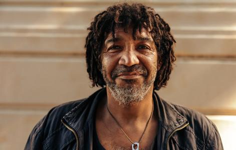Cheerful homeless man looking at the camera