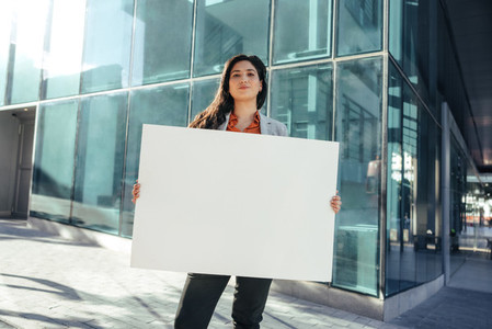 Confident businesswoman holding a white banner outside her workplace