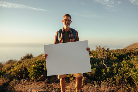 Hiker holding a blank placard on a hilltop