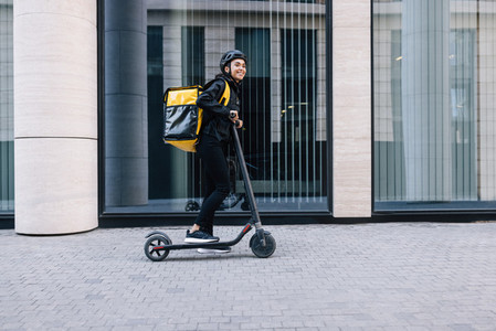 Cheerful female courier standing on electric scooter  Woman in cycling helmet wearing thermal backpack looking away