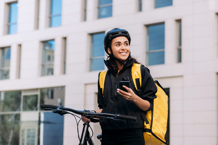 Food delivery woman using smart phone on street in city  Female courier in cycling helmet with backpack looking away
