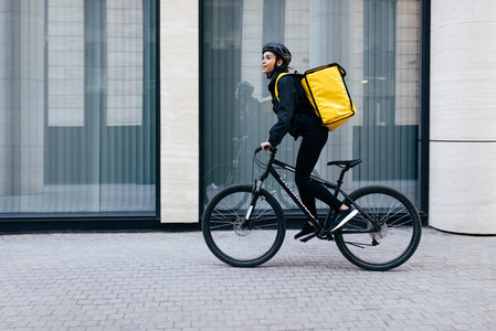 Side view of a young woman riding her bike in the city  Courier with a thermal backpack in her way to deliver food to a customer