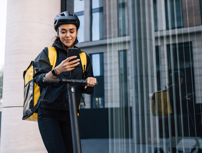 Smiling delivery woman with backpack looking on smartphone leaning on a handlebar of electric push scooter