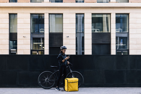Side view of delivery woman holding a mobile phone  wearing a cycling helmet  Young female standing in the city with bicycle and thermal backpack