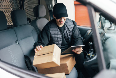 Smiling male courier in uniform and cap checking information on cardboard box while sitting in a car using a digital tablet