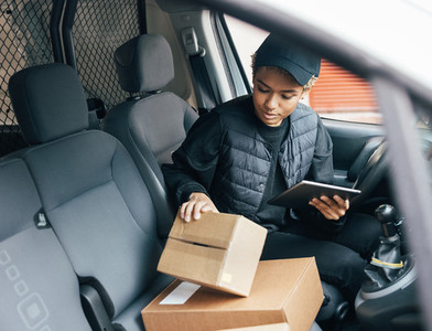 Woman courier checking information on cardboard box while sitting in a car using a digital tablet