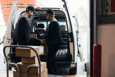 Back view of two delivery people checking information on a digital tablet while standing at van trunk near a warehouse