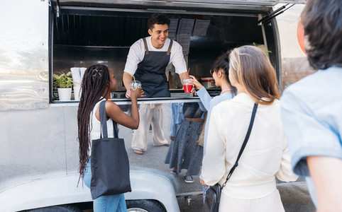 Queue of people to the food truck  Smiling salesman gives drinks to customers