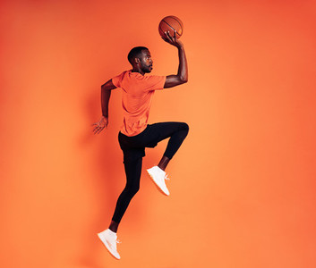 Side view of a sportsman with basket ball exercising against orange background