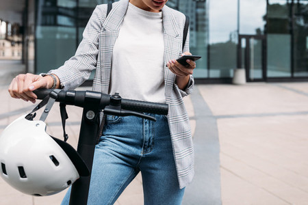 Unrecognizable businesswoman standing at office building with electric scooter holding smartphone