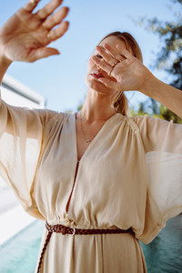 Fashionable woman blocking her face with her hands outdoors