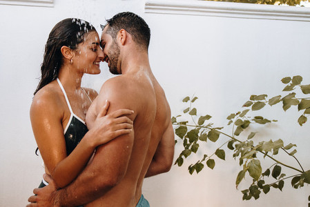 Couple flirting under the shower outdoors