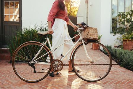 Young woman pushing a bike outdoors