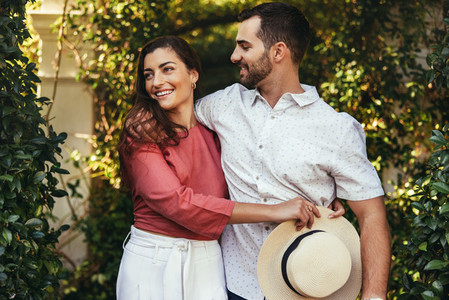 Smiling young couple embracing each other outdoors