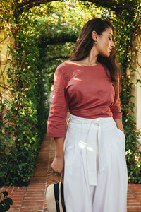 Elegant young woman standing in a plant tunnel
