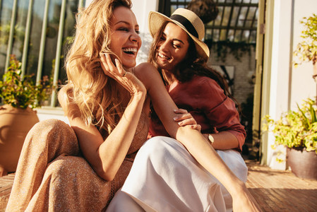 Two girlfriends laughing together outside a hotel