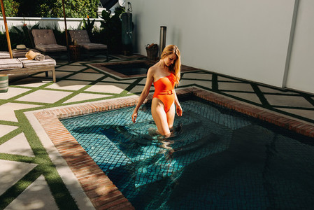 Woman stepping into a swimming pool at a spa