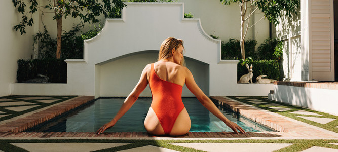 Carefree woman sitting by the pool in red swimwear