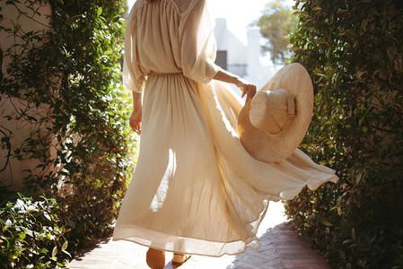 Unrecognizable tourist woman walking in a flowy dress outdoors