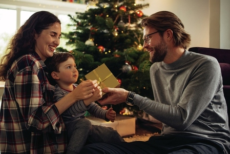 Family exchanging Christmas presents at home