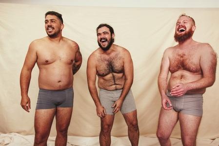 Three shirtless men laughing in a studio