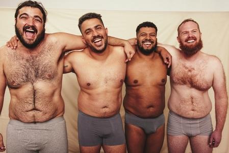 Studio shot of shirtless men embracing each other