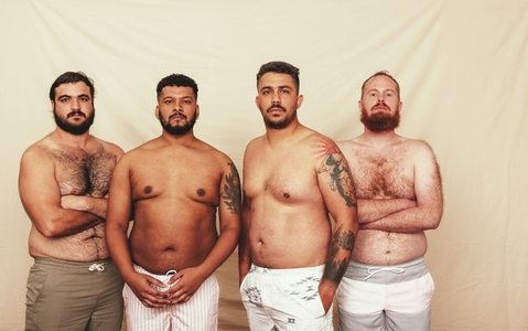 Men standing together in a studio without shirts