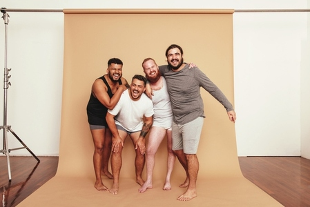 Male friends laughing together in a studio