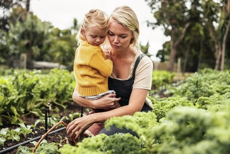 Mother carrying her daughter while gathering vegetables