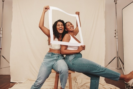 Best friends laughing through a white picture frame