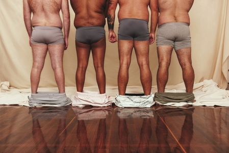 Anonymous men standing with their shorts dropped down