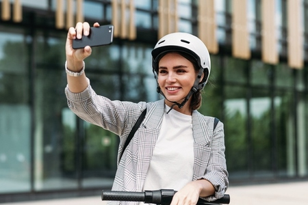 Smiling businesswoman making selfie on her smartphone while standing in the city with electric scooter