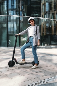 Young cheerful woman standing in the city with electric push scooter