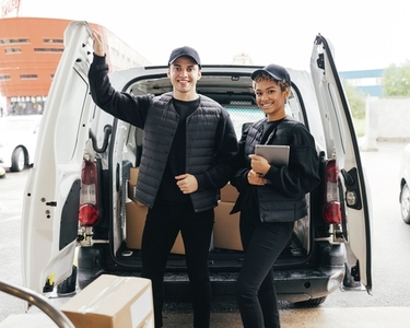 Portrait of two young couriers in uniform standing at van trunk and looking at camera