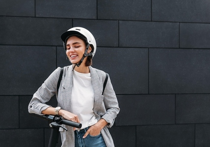 Stylish woman laughing with closed eyes while standing outdoors with electric scooter