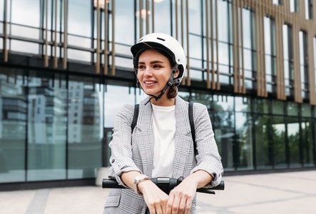 Beautiful smiling woman wearing cycling helmet looking away while standing in the city