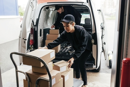Two people in uniform loads parcels in van  Woman taking boxes from cart