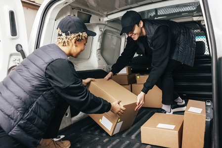 Two people working for delivery company unloading cardboard boxes from van