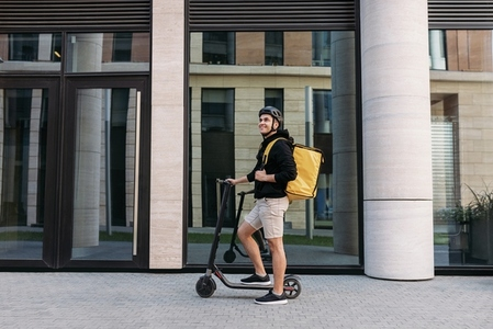 Smiling messneger man standing outdoors with electric push scooter  Delivery man with termal backpack in the city