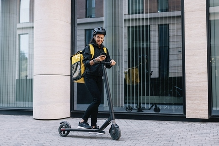 Delivery woman using smartphone while standing in the city with electric push scooter