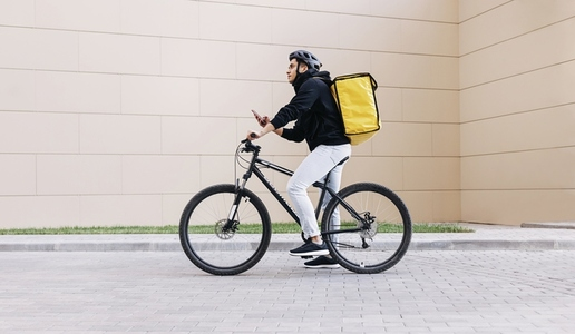 Side view of a young messenger with termal backpack man riding his bike and using mobile phone in the city